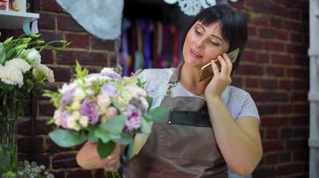 flower shops : Female florist talking on phone discussing cost of bouquet with customer in a flower shop. Ribbons, flowers, calculator on working table. shopping, sale, floristry and consumerism concept Stock Footage
