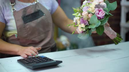 virágárus : Female florist counting cost of bouquet with calculator in a flower shop closeup. Ribbons, flowers, calculator on working table. shopping, sale, floristry and consumerism concept Stock mozgókép