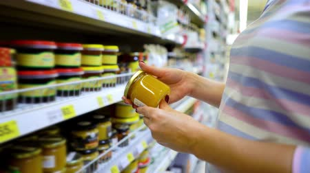 описание : Closeup caucasian woman hand near shop shelves choosing light honey jar in grocery market. female customer checking product ingredients. supermarket, sale, shopping, assortment, consumerism concept