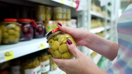описание : Closeup caucasian woman hands near shop shelves choosing green olives jar in grocery market. female customer checking product ingredients. supermarket, sale, shopping, assortment, consumerism concept