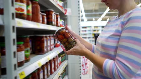 описание : Caucasian woman near shop shelves choosing marinade tomatoes jar in grocery market. female customer checking product ingredients. supermarket, sale, shopping, assortment, consumerism concept