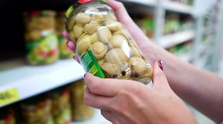 описание : Closeup caucasian woman hands near shop shelves choosing mushrooms jar in grocery market. female customer checking product ingredients. supermarket, sale, shopping, assortment, consumerism concept
