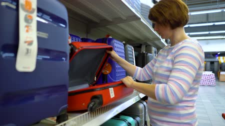 consumerism : Caucasian woman near shop shelve choosing suitcase in haberdashery market. female customer checking product assortment preparing to journey. supermarket, sale, shopping, consumerism, traveling concept Stock Footage