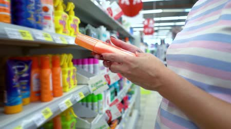 описание : Closeup caucasian woman near shop shelves choosing cosmetics in market. female customer checking sunscreen cream ingredients. beauty, health, skin care, sale, shopping, assortment, consumerism concept Стоковые видеозаписи