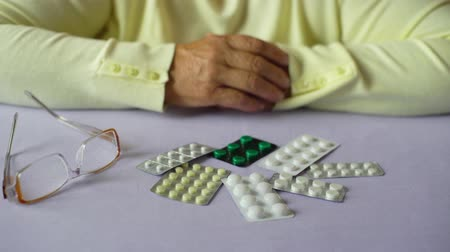 doente : Closeup senior woman hands with pills and eyeglasses on table at home. Age, medicine, health care, treatment, pension, people concept