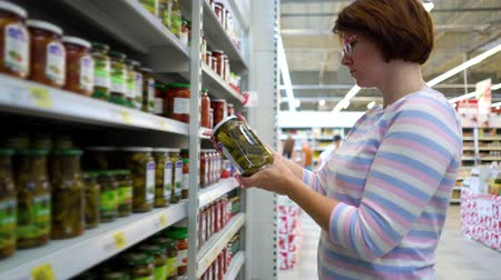 описание : Caucasian woman near shop shelves choosing marinade cucumbers jar in grocery market. female customer checking product ingredients. supermarket, sale, shopping, assortment, consumerism concept