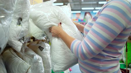 по уходу за телом : Caucasian woman near shop shelve choosing pillow in store. female customer checking textile product assortment. hygiene, body care, sale, shopping, consumerism, household concept
