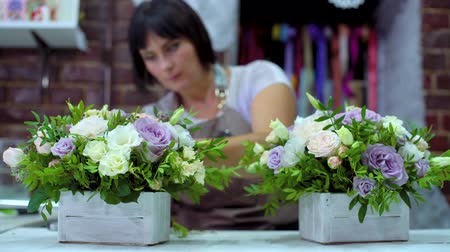 bud rose : professional florist arranging beatiful flower composition in wooden box in floral design studio. Caucasian female master in apron creating floral design. Floristry, handmade, small business concept