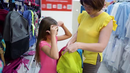 описание : Caucasian mother and daughter choosing school bag backpack in haberdashery market. female customers checking product assortment preparing to academy. sale, shopping, consumerism, education concept