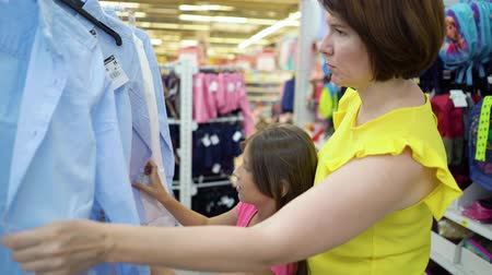описание : Caucasian mother and daughter choosing shirts in market. female customers checking product assortment preparing to academy. sale, shopping, consumerism concept Стоковые видеозаписи