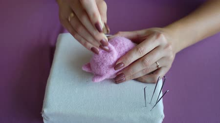 piglet : closeup young caucasian woman hands making wool dry felting tutorial. female showing needle felted toy master class. Hobby, handmade, crafting, leisure, teaching, education, creativity, design concept Stock Footage
