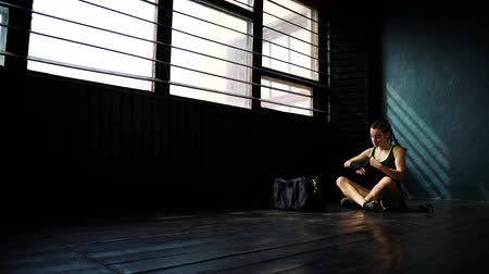 sitting floor : Panning young woman sitting on floor and wrapping hands with boxing wraps in fitness club. Fit female boxer preparing to exercise. Wellness, fighting, motivation, martial arts, self defense concept