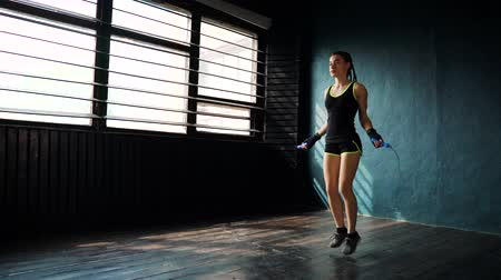 skákání : Young purposeful female boxer in wrapped bandage hands jumping on skipping rope in gym. Fit woman preparing to boxing competition. Wellness, fighting, motivation, martial arts, self defense concept Dostupné videozáznamy