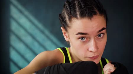 self defense : closeup portrait beautiful young boxing woman training punching in fitness studio. Fit female preparing to boxing competition. Wellness, fighting, motivation, martial arts, self defense concept Stock Footage