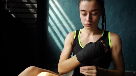 bandagem : Slowmotion panning fit young woman sitting on floor and wrapping hand with bandage. Female boxer athlete preparing for boxing training. wellness, fighting, motivation, self defense concept