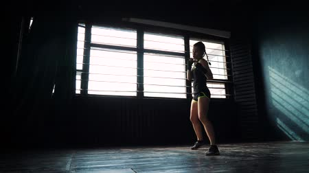 átlyukasztás : silhouette beautiful young boxing woman training punching in fitness studio. Fit female preparing to boxing competition. Wellness, fighting, motivation, martial arts, self defense concept