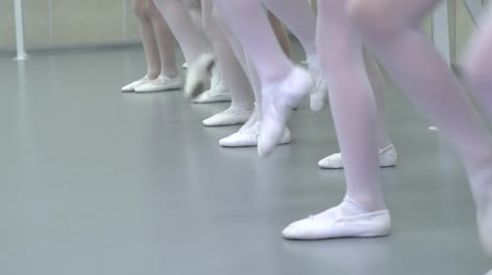 papucs : closeup legs of little ballerinas group in white shoes in row practicing in ballet studio slow motion. Young girls training elements of classical dance exercise. Childhood, dancing, lifestyle concept