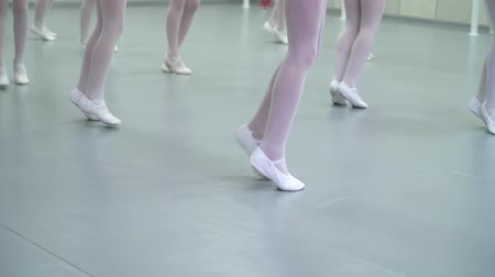 тапки : closeup legs of little ballerinas group in white shoes practicing in ballet school, slow motion. Young girls training elements of classical dance exercise. Childhood, dancing, lifestyle concept