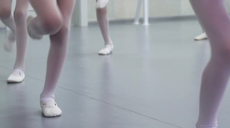 тапочка : closeup legs of little ballerinas group in white shoes practicing in ballet studio, slow motion. Young girls training elements of classical dance exercise. Childhood, dancing, lifestyle concept
