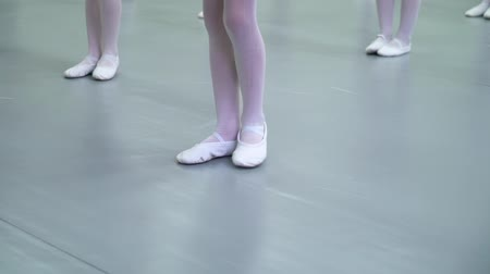 fegyelem : closeup legs of little ballerinas group in white shoes practicing in ballet school, slow motion. Young girls training classical dance exercise. Childhood, dancing, lifestyle concept