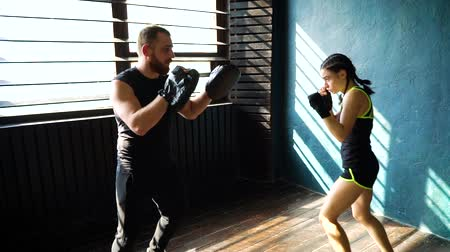 delgado : Panning shot of fit white female boxer training with boxing coach at gym. Young slender brunette girl practicing with trainer. Wellness, healthy lifestyle, combat, motivation, cardio workout concept
