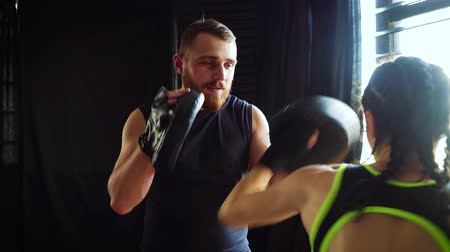 instrutor : boxing coach training fit white female boxer at gym in slow motion. bearded instructor in mitts working with girl athlete. Wellness, competition, combat, motivation concept