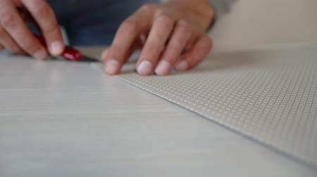 papeteria : closeup male hands preparing new bended wallpaper roll with stationery knife on table indoor. Cutting preparation in repair apartment. renovation, design concept Wideo