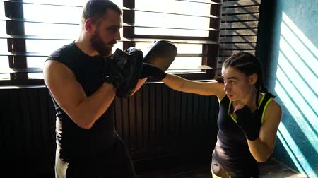 trener : Panning shot of fit white female boxer training with boxing coach at gym. Young slender brunette girl practicing with trainer. Wellness, healthy lifestyle, combat, motivation, cardio workout concept