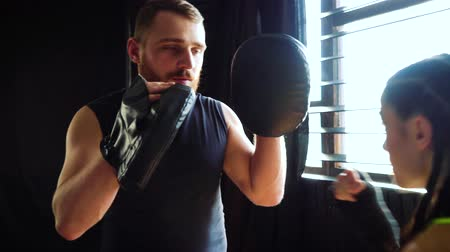 bokser : boxing coach training fit white female boxer at gym in slow motion. bearded instructor in mitts working with girl athlete. Wellness, competition, combat, motivation concept
