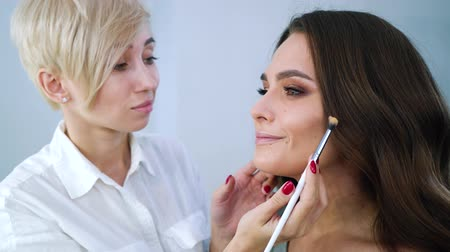 femininity : closeup of female makeup artist applying cosmetics on young beautiful woman face with brush at beauty salon. people, cosmetics, care, lifestyle, style concept Stock Footage