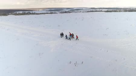 snowboarder : aerial of group of snowboarders with equipment in hands walking on snow hills with copy space and free space. winter sport, friendship, healthy lifestyle Stock Footage