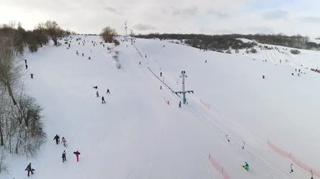 сноуборд : aerial of skiers and snowboarders sliding down snowy slope and riding up with ski lift. winter sports, leisure activities, healthy lifestyle