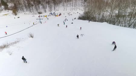 snowbord : aerial of skiers and snowboarders sliding down snowy slope and riding up with ski lift. winter sports, leisure activities, healthy lifestyle