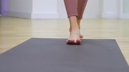 sakk : view of young woman feet unrolling mat and stepping on it in slow motion. Sports, recreation, health concept