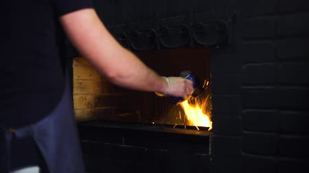 firebox : young man in apron kindles fire in restaurant oven with air blower. barbecue, food preparation Stock Footage