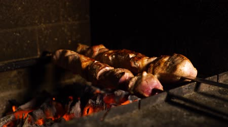 espetos : closeup of skewers with pork meat turning while roasting in wood fired oven. barbecue, grill, food preparation