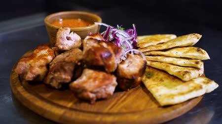 espetos : closeup view of roasted meat, tortillas, sauce, chopped onion on wooden cutting board with rack focus. food preparation, healthy eating Stock Footage