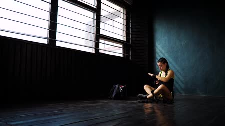 bandaj : panning slow motion fit young woman sitting on floor, wrapping hand with bandage tape. Female boxer athlete preparing for boxing training. wellness, fighting, motivation, self defense concept Stok Video