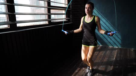 wrapped up : Slow motion young serious female boxer in wrapped hands warming up, jumping on skipping rope in gym. Fit woman preparing to boxing competition. Wellness, fighting, motivation, self defense concept Stock Footage