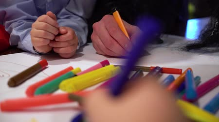 marker : closeup kids hands drawing together on big paper with focus on colored markers Stock Footage