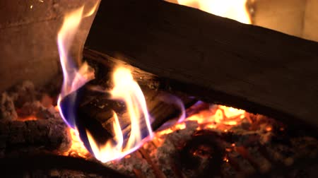 firebox : closeup of burning wood in traditional brick fireplace in the dark