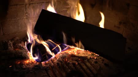 firebox : closeup of wood logs burning in traditional fireplace in the dark