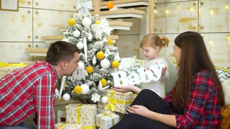caráter : little girl plays with wooden word baby near parents at Christmas time at home Stock Footage