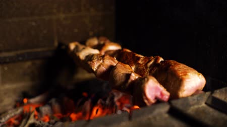 mariníroz : closeup of smoked meat roasting on skewers in traditional wood fired oven