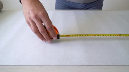 decorador : closeup male hands measuring wallpaper roll with measure tape on table indoor