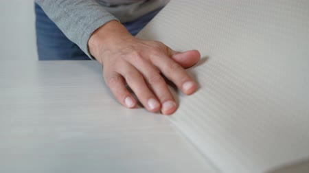 decorador : closeup male hands preparing new wallpaper roll bending on table indoor