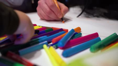 yaşam tarzı : closeup children drawing together on paper sheet with focus on colored markers Stok Video
