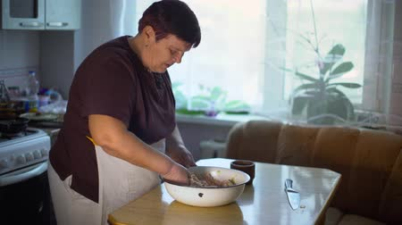 mixing bowl : senior woman mixing ingredients for traditional dish in a bowl Stock Footage