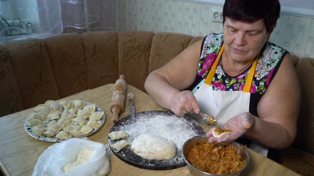 капуста : senior woman making dumplings with roasted cabbage stuffing