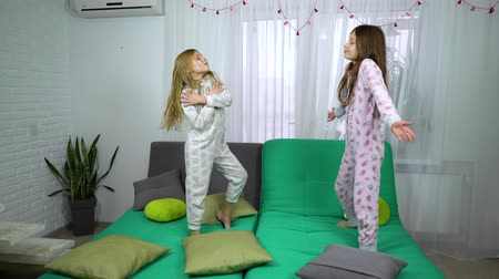 ugrás : two girls in pajamas dancing on sofa